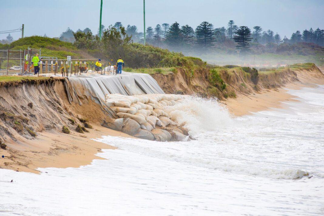 Waves smash against emergency sandbags at Stockton Beach.