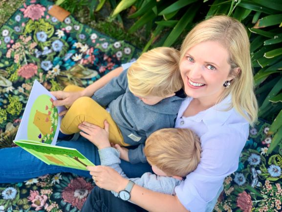 woman with two children in her lap reading a book
