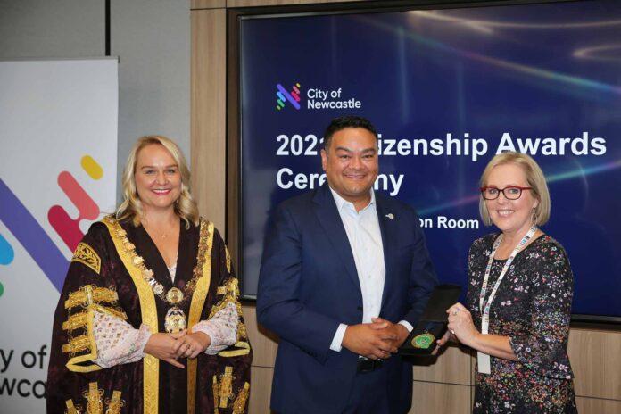 three people holding awards