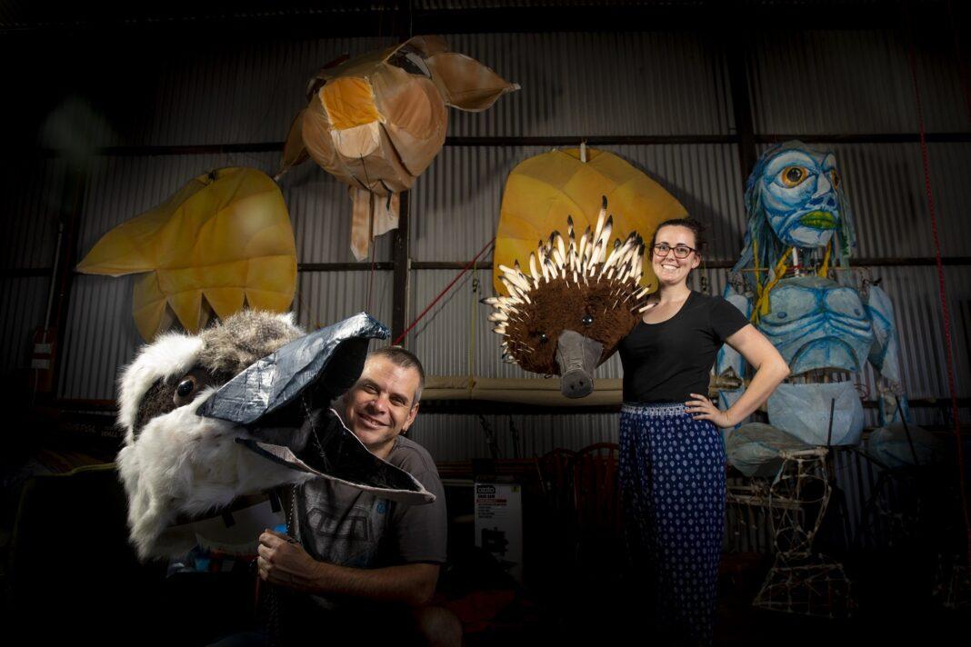 two people holding large animal masks