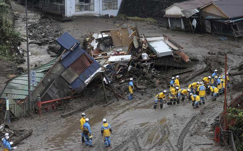 Teams of around 20 rescuers sorting through mudslide rubble in Japan